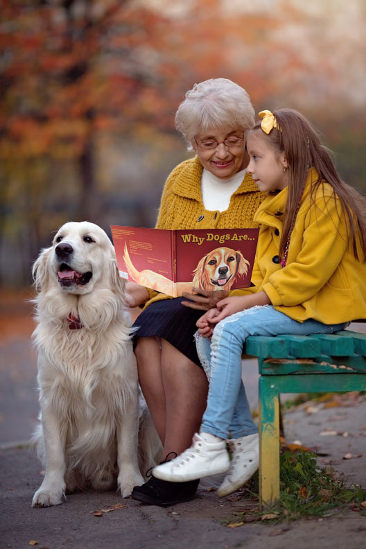 Grandma and girl reading Why Dogs Are, childrens book